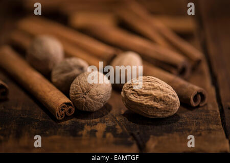 Cinnamon sticks and whole nutmeg on a rustic wooden surface. - Stock Photo