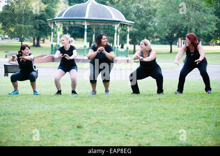 Five happy white women in black gym clothes put through their paces in an outdoor bootcamp early in the morning - Stock Photo
