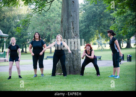 Five women in black gym clothes put through their paces in an outdoor bootcamp early in the morning in a public - Stock Photo