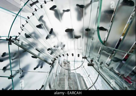 Glass spiral staircase with people and skyscrapers from below, Manhattan, New York City, New York, United States - Stock Photo