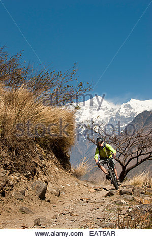A mountain biker in Nepal with views of Sringi Himal in the distance - Stock Photo