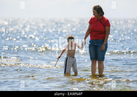 Mother holds hands with her young son while wading in the ocean - Stock Photo