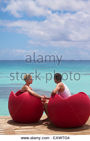 Two honeymooners enjoy a moment in the sun on a dock in the Tuamotu Archipelago. - Stock Photo