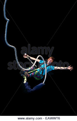 A girl smiles for the camera while bouncing back on a bungee jump at The Last Resort in Nepal - Stock Photo