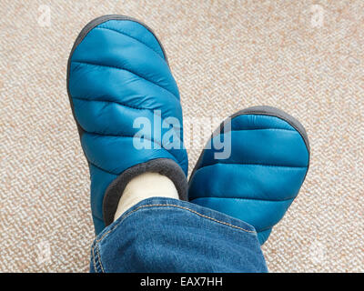 A woman with feet crossed wearing a pair of jeans and warm padded slippers on the carpet at home. England, UK, Britain - Stock Photo