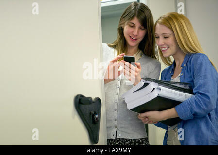 Women looking at smartphone in office - Stock Photo