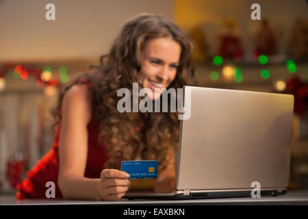 Closeup on happy young woman with credit card using laptop - Stock Photo