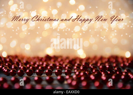 Yellow Christmas lights background with red pearls on wooden floor and text effect - Stock Photo