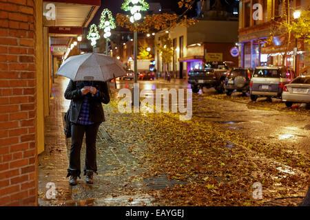 Woman on cellphone with umbrella on downtown street on rainy night-Victoria, British Columbia, Canada. - Stock Photo