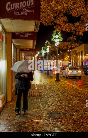 Woman on cellphone with umbrella on downtown street on rainy night-Victoria, British Columbia, Canada. - Stockfoto