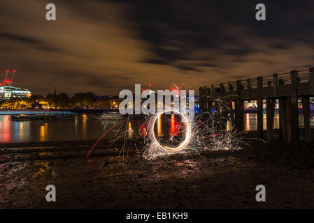 Light painting, spinning lit steel wool on a Thames beach at night - Stock Photo