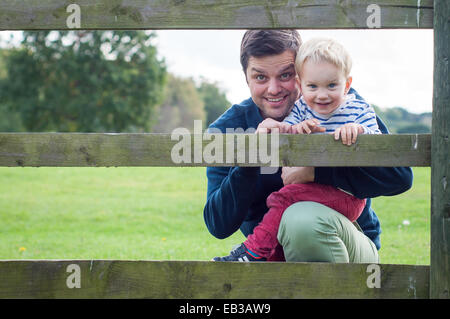 Portrait of father and son looking through fence - Stock Photo