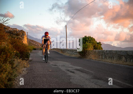 France, Corsica, Road cycling above sea at sunset - Stock Photo