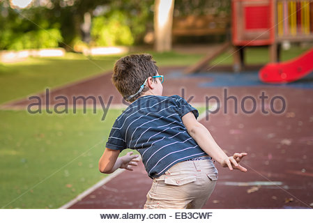 Spain, Valencia, Boy(8-9) playing hide-and-seek in playground - Stock Photo