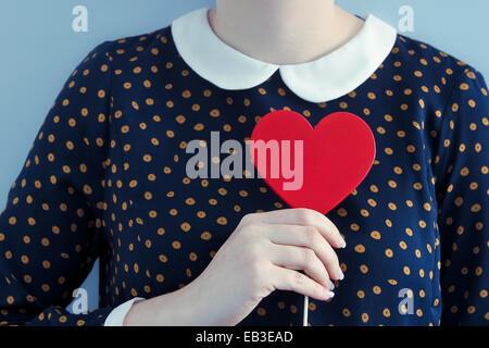 Woman wearing polka dot dress holding heart shape object - Stock Photo