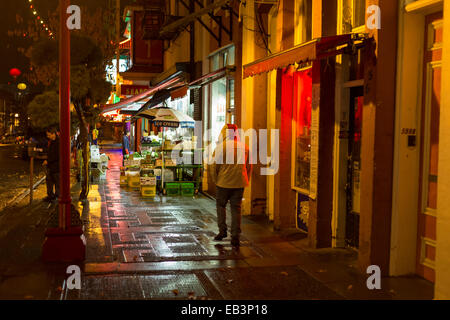 Man with hood on jacket up walking in Chinatown on rainy  night-Victoria, British Columbia, Canada. - Stock Photo