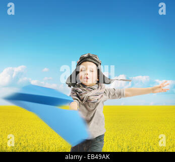 Little boy playing the blue paper plane - Stock Photo