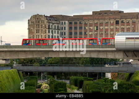 A Docklands Light Railway train passing derelict Docklands warehouse, Millennium Mills in East London - Stock Photo