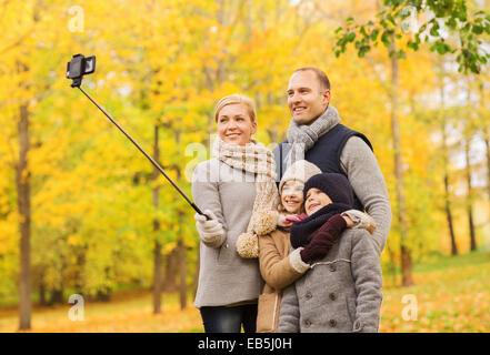 happy family with smartphone and monopod in park - Stockfoto
