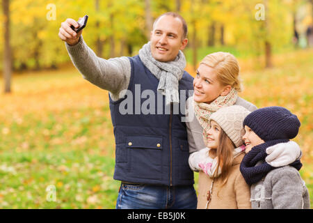 happy family with camera in autumn park - Stockfoto