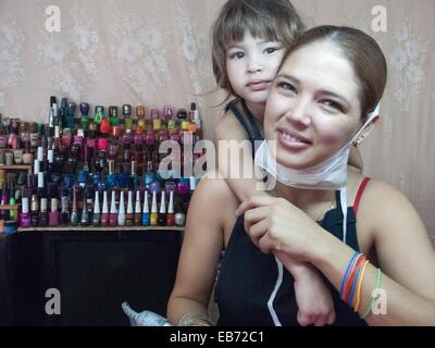 Mom taking break with her daughter from doing a manicure - Stock Photo