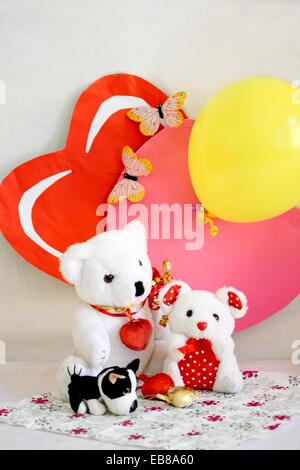 Two Valentine Bears sit on printed napkin with two paper hearts as backdrop  One heart is pink and the other is - Stock Photo