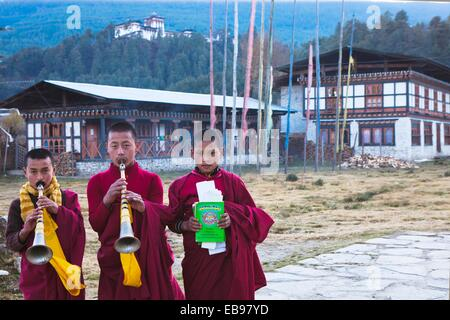 Novice monks with flutes Rgya-Gling outside the temple of Wangdichholing Palace built in 1857 as the Kingdom's first - Stock Photo