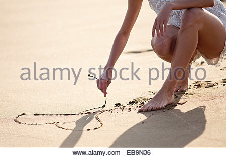 Woman Drawing Heart on Sand - Stock Photo