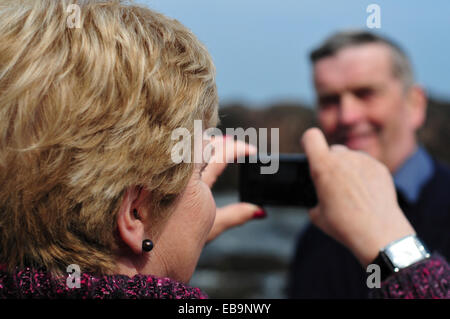 Woman Taking Photo of Man with Smart Phone - Stock Photo