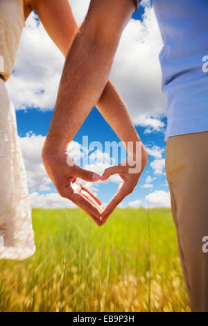 Couple Making Heart Shape with Hands in Field, Cropped view - Stock Photo