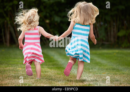 Back View of Two Young Girls Running in Garden Holding Hands - Stock Photo