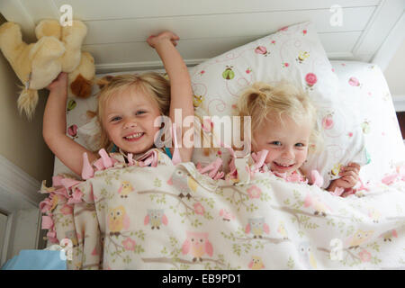 Two Young Girl Lying in Bed Smiling - Stock Photo