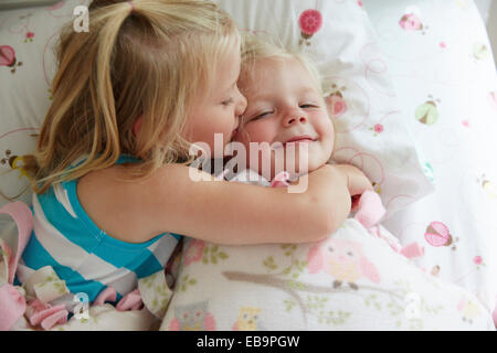 Two Young Girl Lying in Bed Kissing and Cuddling - Stock Photo