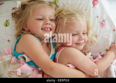 Two Young Girl Lying in Bed Cuddling - Stock Photo