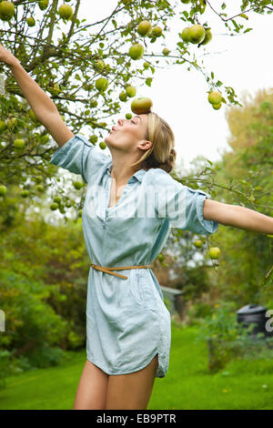 Woman in Orchard Balancing Apple on her Forehead - Stock Photo