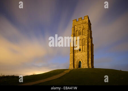 Glastonbury Tor, Somerset, illuminated by the warm glow of street lighting from the nearby town on a cloudy night. - Stock Photo