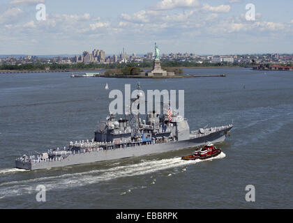 New York Harbor (May 24, 2006) - The USS Anzio CG-68  pass the beloved symbol of freedom, the Statue of Liberty - Stock Photo