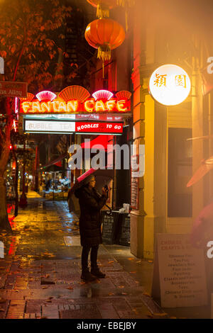 Chinese woman photographing Fan Tan alley entrance in Chinatown on rainy night-Victoria, British Columbia, Canada. - Stockfoto