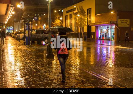 Young woman walking through downtown on rainy night-Victoria, British Columbia, Canada. - Stock Photo