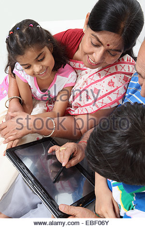 Indian old couple with their grandchild using a digital tablet - Stock Photo
