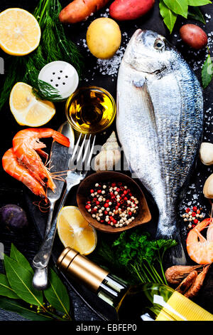 Delicious fresh fish and seafood on dark vintage background. Fish, cockles and shrimps with aromatic herbs, spices - Stock Photo