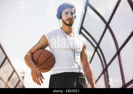 Young male basketball player walking along footbridge listening to headphones - Stock Photo