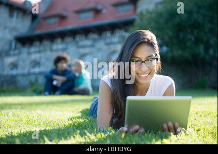 Young woman lying on grass using digital tablet - Stock Photo
