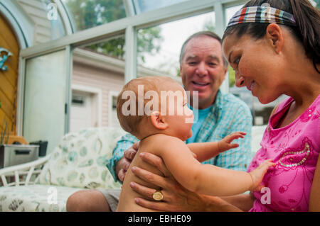 Mother with baby daughter and grandfather in conservatory - Stock Photo