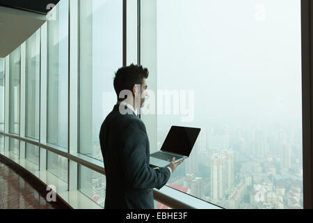 Young businessman with laptop looking out of skyscraper office window, Shanghai, China - Stockfoto
