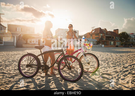 Two women cyclists chatting on beach, Mission Bay, San Diego, California, USA - Stockfoto