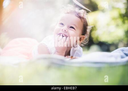 Baby girl lying on blanket in garden - Stock Photo