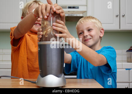 Brothers blending fruits in kitchen - Stock Photo
