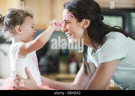 Mother and daughter playing in kitchen - Stock Photo