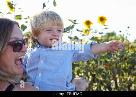 Mid adult woman and toddler son pointing in sunflower field - Stock Photo